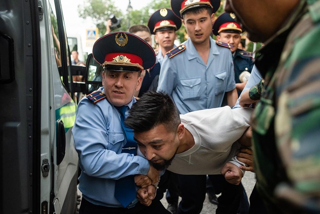 Димаша Альжанова сажают в полицейский микроавтобус 12 июня. (Фото: Данил Усманов)